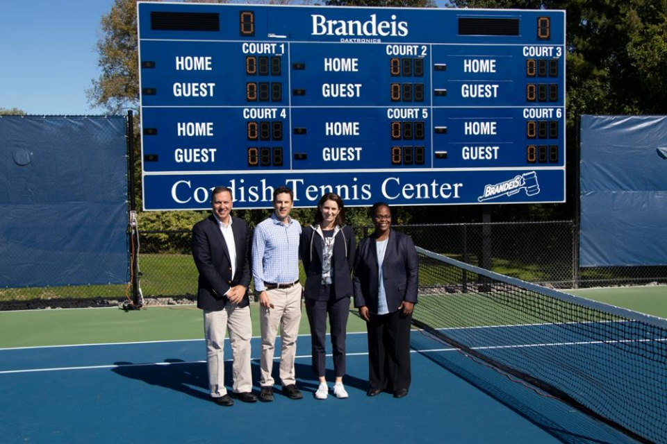 From left to right, President Ron Liebowitz, Jon Cordish, Melissa Fishman Cordish, Lauren Haynie, and Director of Athletics stand in front of the new Brandeis Cordish Tennis Center tennis scoreboard