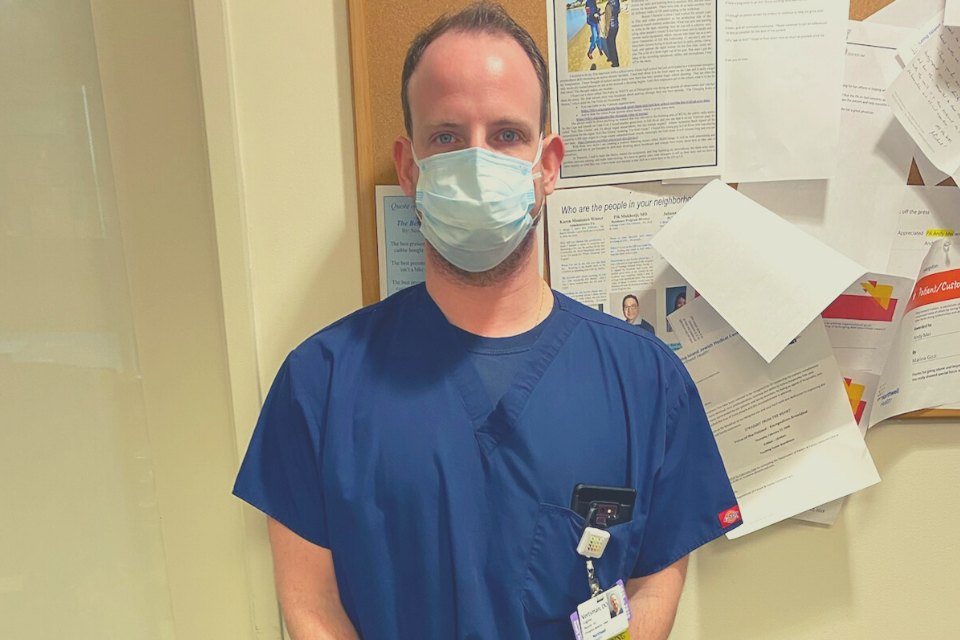 doctor wearing a face mask stands in front of bulletin board