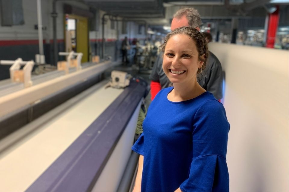 Stephanie Fodor MacDonald stands in a textile warehouse and smiles